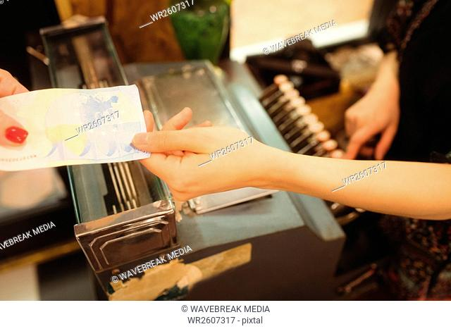 Female cashier accepting a payment at counter