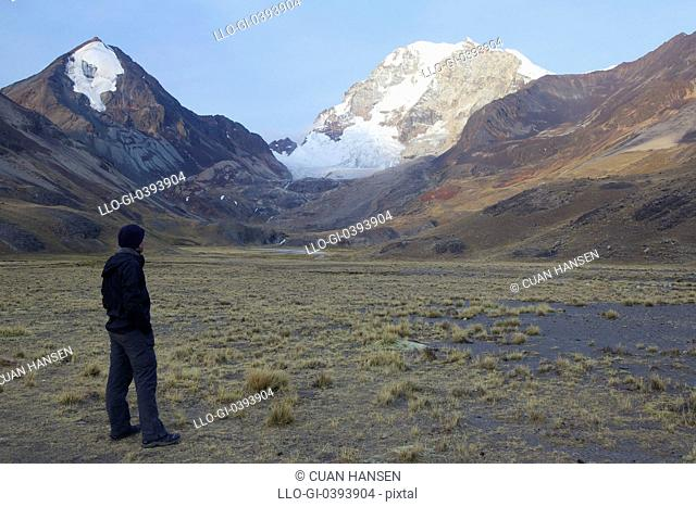 View of trekker at sunset observing Huayna Potosi, Cordillera Real, Andes Mountains, Bolivia, South America