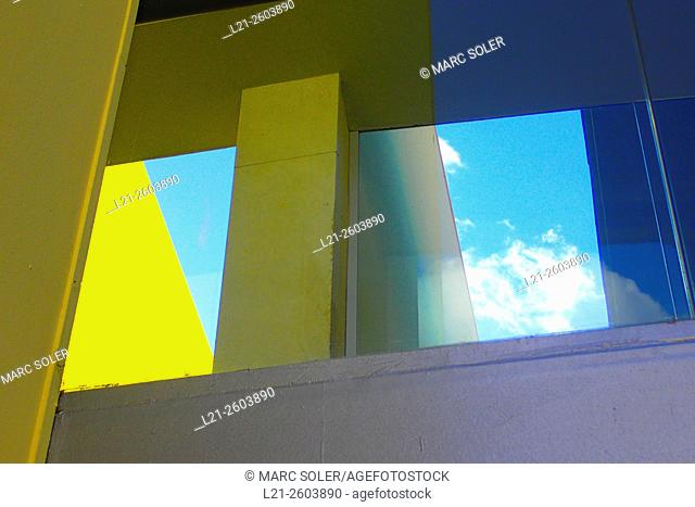 Detail of a building, yellow wall, blue sky and white cloud. Barcelona, Catalonia, Spain