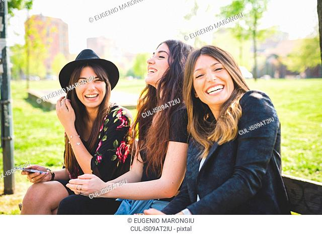 Portrait of three young female friends laughing in park