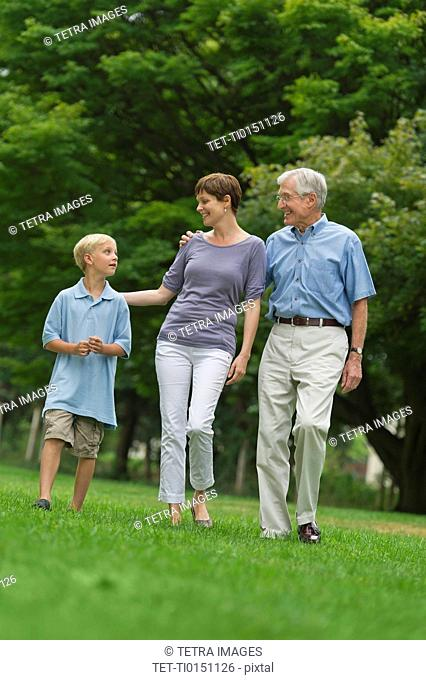 Three generation family walking in park