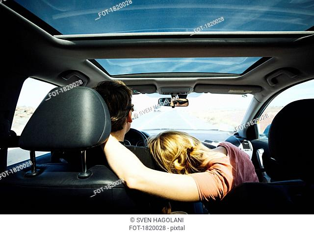 Affectionate couple riding in sunny car