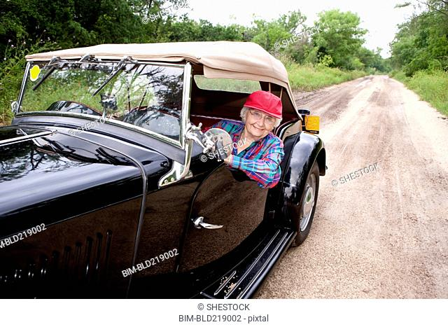 Older Caucasian woman driving convertible on rural road