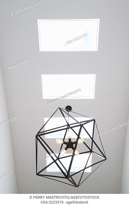 Skylight windows and black steel hexagonal lighting fixture with five clear glass bulbs hung above the staircase inside a modern cube style home