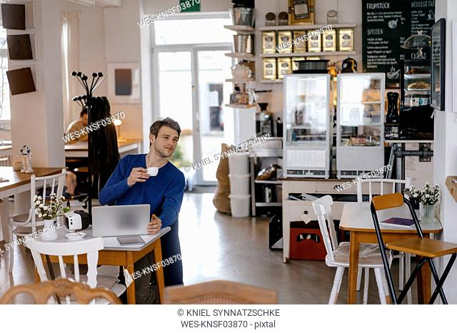 Man sitting at table in a cafe with laptop
