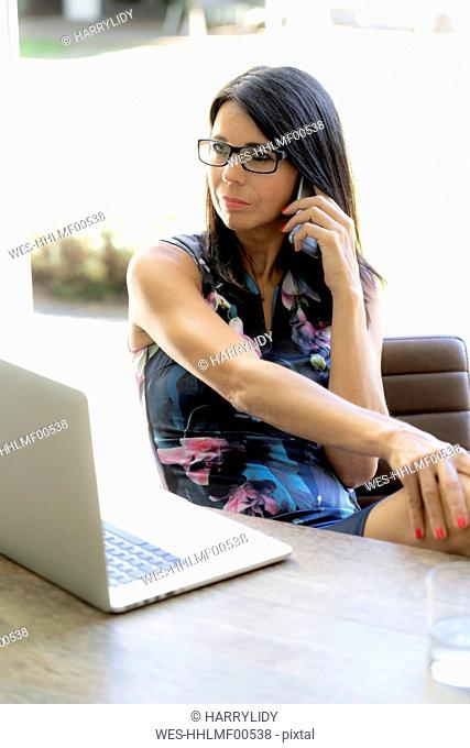 Dark-haired woman on the phone at desk