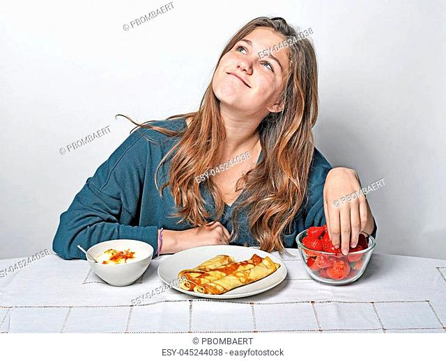 Cute girl sitting at breakfast table eating pancakes and strawberries