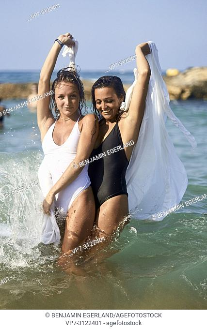 two lively women in white blanket sheet, playful, dancing in sea, best friends, friendship goals, holidays, adventure, water, splashes