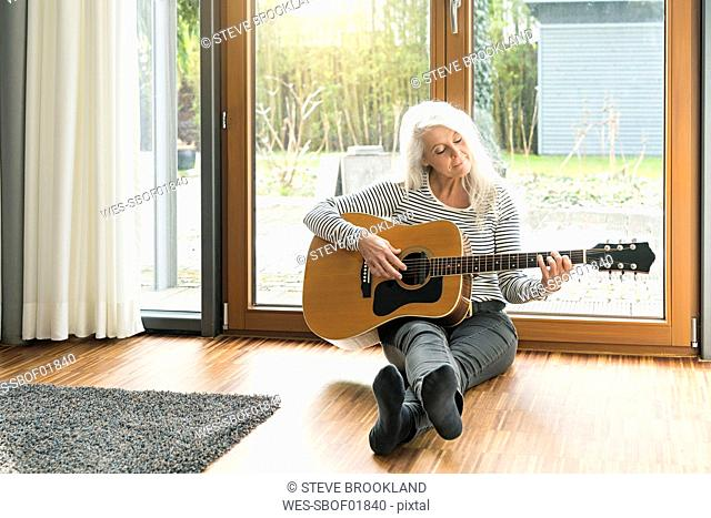 Mature woman sitting on the floor of living room playing guitar