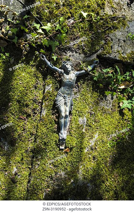 metal figurine showing crucified jesus christ lying on moss-covered stone , paris, ile de france, france