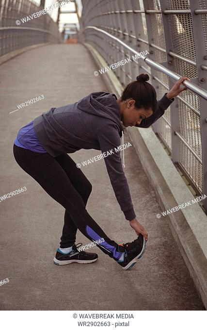 Woman stretching legs by railing on bridge