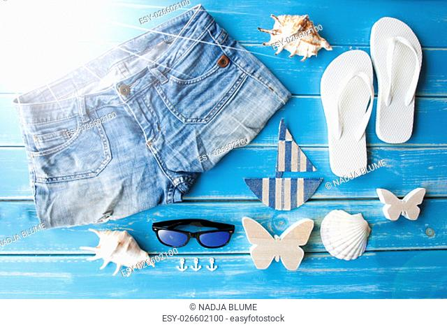 Blue Wooden Background With Summer Decoration Like Clothes, Shells And Sailboat. Sunny Summer Greeting Card. Holiday Vacation Feeling