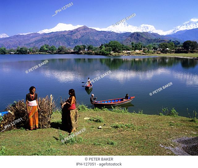 Nepalese country women with large bundles of firewood on the banks of Lake Phewa Tal overlooked by Fishtail Mountain