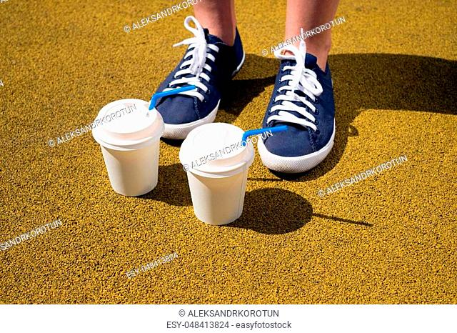 Female feet in blue sneakers and two cups of coffee on yellow coating on a sunny day