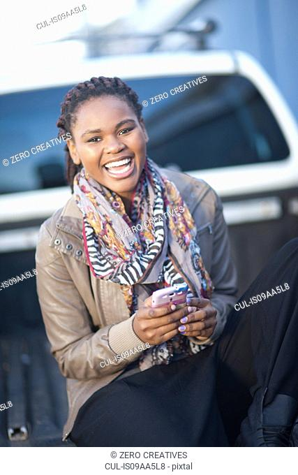 Portrait of young female sitting on back of pickup truck