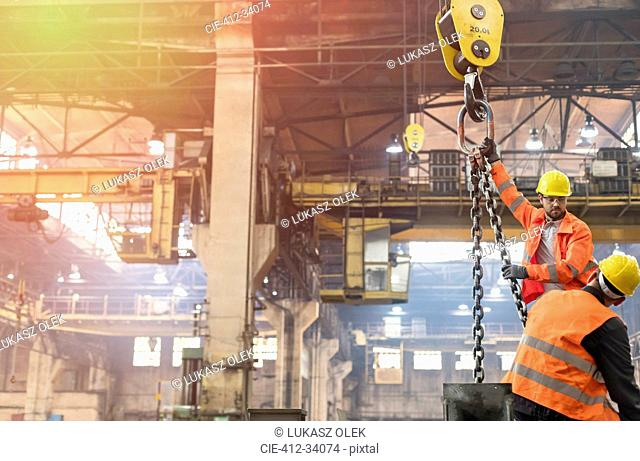 Steel workers operating crane in factory