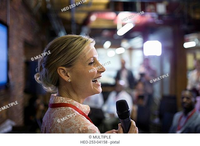 Close up businesswoman with microphone speaking at conference