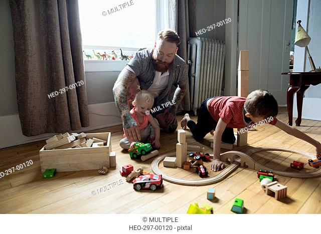 Father and children playing with wood blocks and toy train on floor
