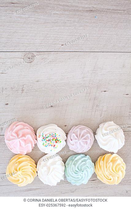Top view of meringues in pastel colors, food background with copy space