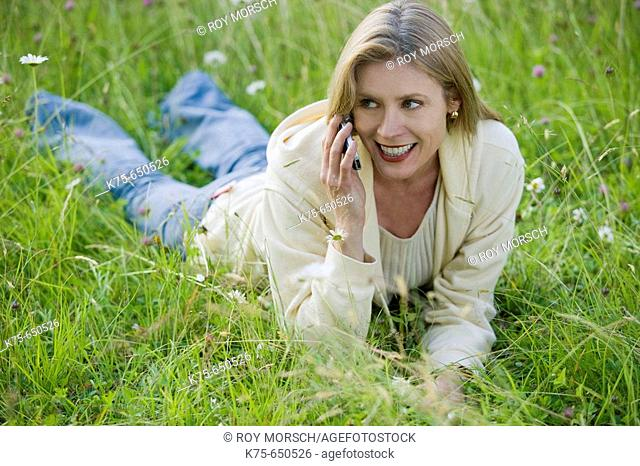 woman using cell phone in meadow