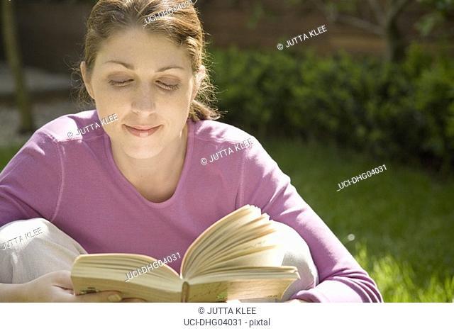 Woman reading book in garden