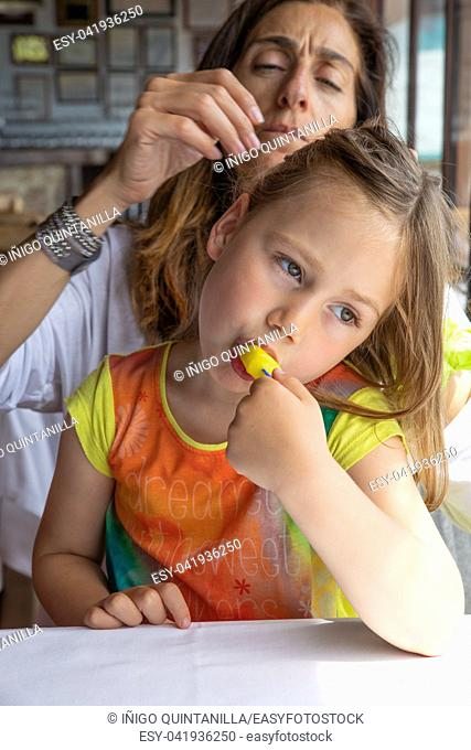 four years old blonde little cute girl eating ice lolly sitting on mother legs in restaurant