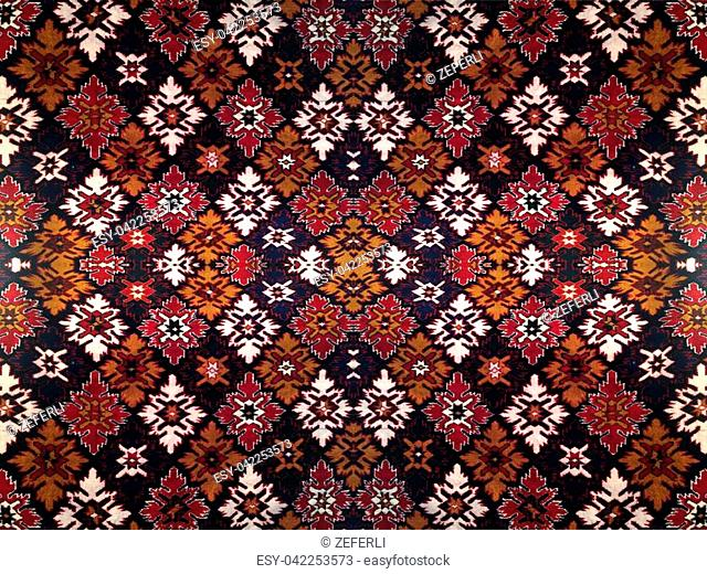 Fragment of ornamental carpet green blue red pink grey violet yellow orange maroon black white turquoise, or abstract surface of tiled rhombus leaves pattern