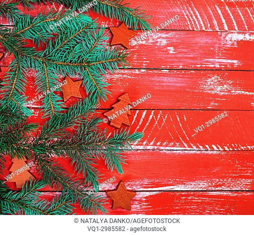 bright red wooden background of boards with green spruce branch and Christmas decor, empty space on the right