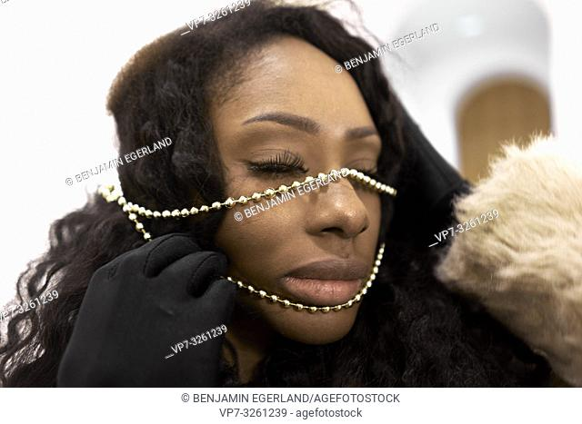 woman with jewellery chain over face, in Munich, Germany