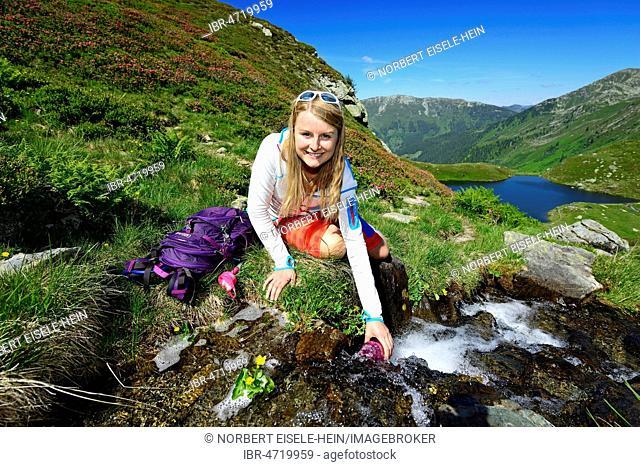 Hiker fills water in the drinking bottle, in the back lake Mittlerer Wildalmsee, Kelchsau, Kitzbühel Alps, Tyrol, Austria