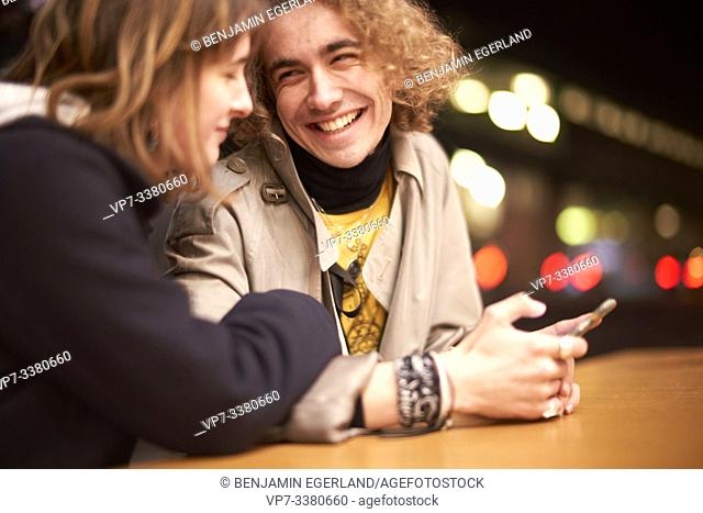 happy man with smartphone smiling at girlfriend at night