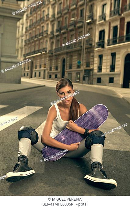 Woman holding skateboard on city street