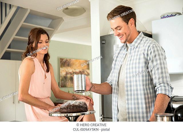 Woman watching man sieve icing sugar over cake
