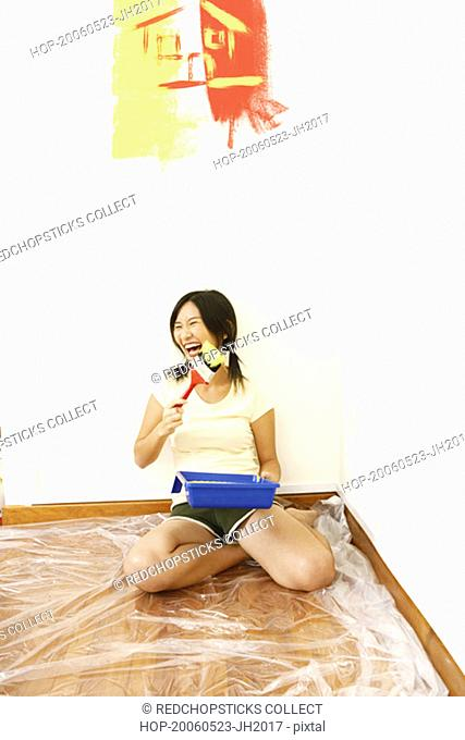 Young woman holding a paintbrush and laughing