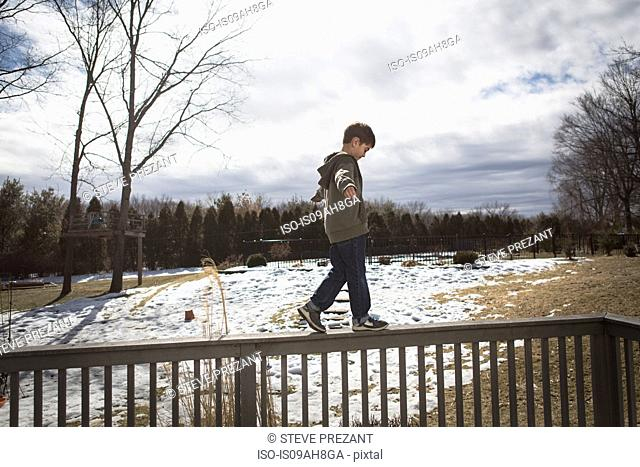 Boy walking along top of fence in park