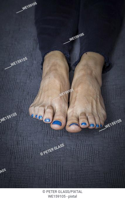 Close-up of a young woman's bare feet with toenail polish on her toes