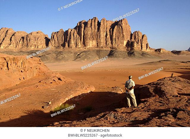 single man standing on a rock looking at the desert Wadi Rum, Jordan