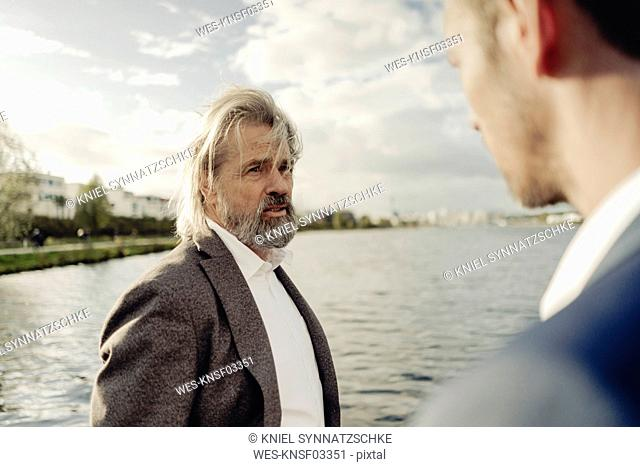 Senior businessman at a lake talking to man in foreground