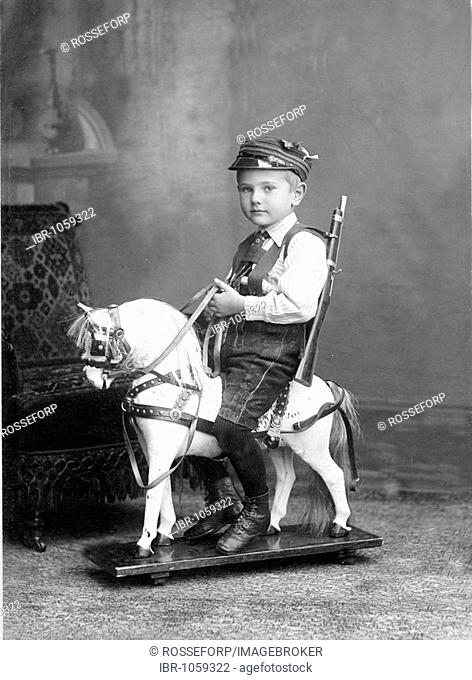 Historic photograph, young boy sitting on a rocking horse, around 1905