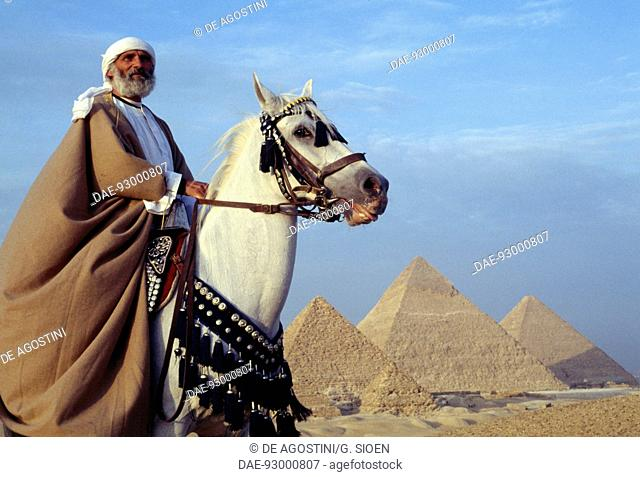 A Bedouin on horseback in front of the pyramids of Cheops, Chephren and Menkaure, Giza Plateau (UNESCO World Heritage List, 1979), Egypt