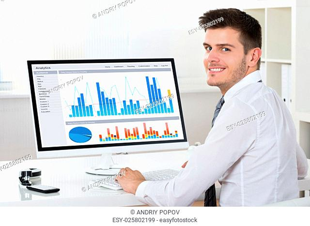 Young Happy Businessman Analyzing Financial Report On Computer At Desk