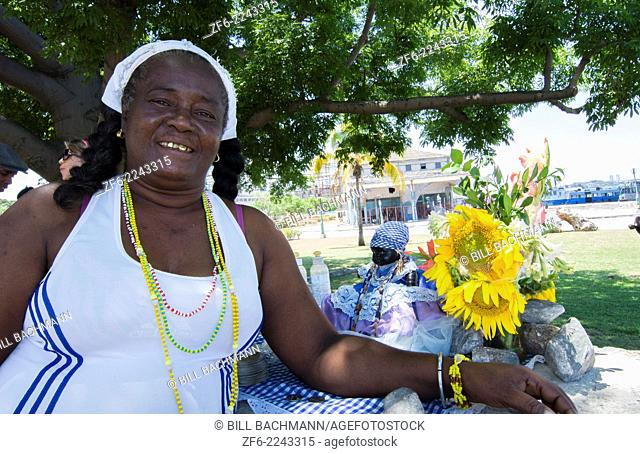 Havana Cuba Santeria woman in white with doll with African religion and catholic in Habana with gold teeth 17