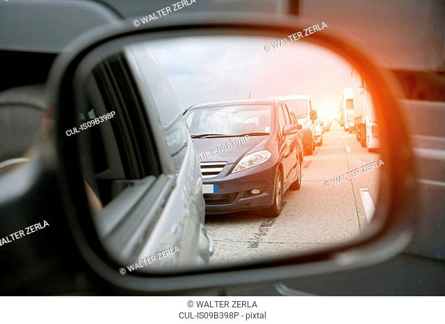 Wing mirror view of rows of traffic queueing on highway