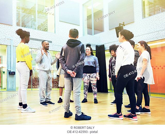 Teenage students listening to male instructor in dance class studio