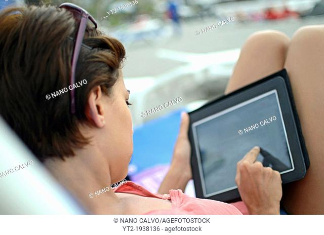 Young attractive woman using tablet in swimming pool