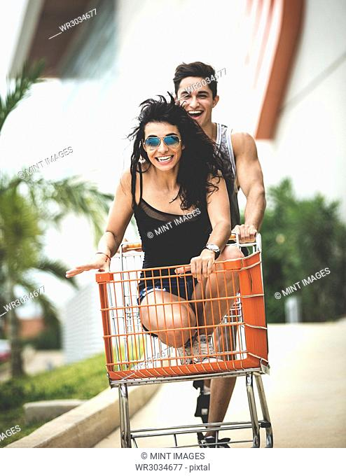 A young man pushing a young woman sitting in a shopping trolley