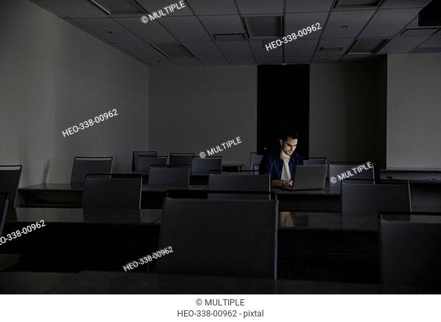 Businessman working late at laptop in dark office classroom