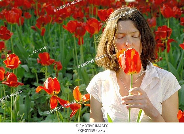 Woman smelling at red tulip