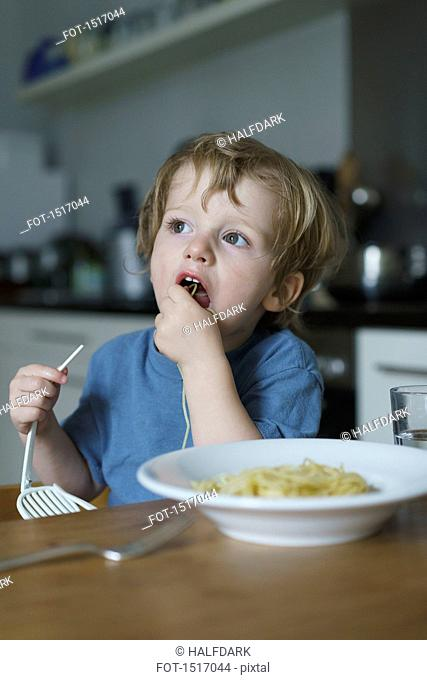 Boy eating noodles in kitchen at home
