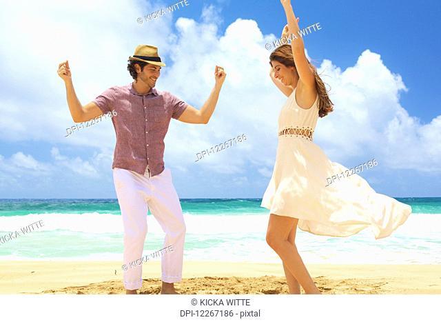 Couple dancing on the beach; Kealia, Kauai, Hawaii, United States of America